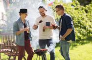 Friends drinking beer at summer barbecue party Stock Photos