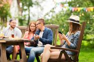 Woman with smartphone and friends at summer party Stock Photos