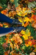 Female legs in boots on ground with autumn leaves Stock Photos