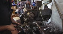 Mechanic working on a lathe machine Stock Photos