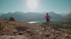 Beautiful girl in sports clothes, training,running in mountainous terrain, slow Stock Footage