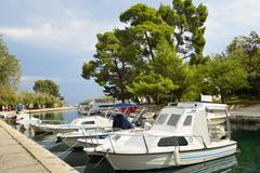 Boats anchor at the seafront in Trogir, Croatia Stock Photos