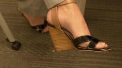 Female with legs crossed wearing high heels rotating her foot Stock Footage