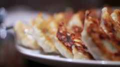 Japanese gyoza with one side burnt crust. Eating by chopsticks Stock Footage