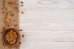 Almonds in a brown bowl and old white wooden table. Stock Photos
