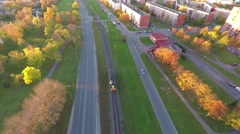 Train rolls through scenic rural city at sunset. Aerial footage. Stock Footage