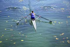 A Young single scull rowing competitor paddles on the tranquil lake Stock Photos