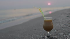 Close up of glass of fruit cocktail on a tropical beach at sunset in the evening Stock Footage
