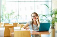 Woman working with a laptop and talking on the cell phone Stock Photos