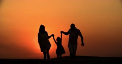 4k silhouette of a family, father mother and little daughter walking on the Stock Footage