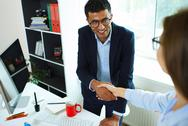 Young businessman and woman shaking hands in office Stock Photos