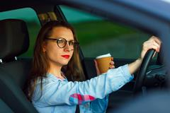 Woman with coffee to go driving her car Stock Photos