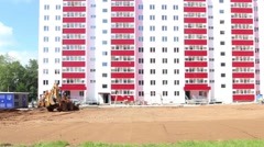 Yellow tractor works near pink building on construction site Stock Footage