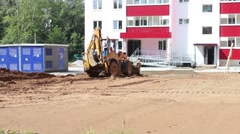 Yellow tractor works on construction site at summer day Stock Footage