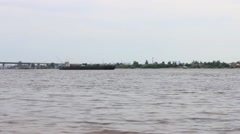 Large cargo ship sails on river with bridge at summer day Stock Footage