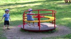 Happy little boy and girl play with carousel in summer green park Stock Footage