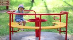 Happy girl having fun on carousel in summer green park Stock Footage