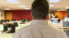 Camera following a man behind his head and shoulders walking through office Stock Footage