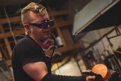 Glassblower shaping molten glass piece with a wet cloth Stock Photos