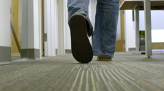 Camera following a man behind his feet walking through an office Stock Footage