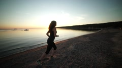 Athletic women running outdoors on promenade at sunset near ocean Stock Footage