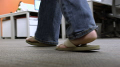 Camera following a man behind his feet walking through an office corridor Stock Footage