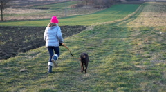 Girl running with dog on the leash in the country, super slow motion Stock Footage