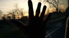 Male hand on window glass in car during sunset, slow motion Stock Footage