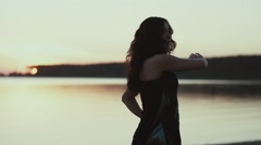 The girl trainings at sunset. Turns body, warm hands Stock Footage
