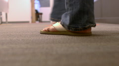 Camera following a man behind his feet walking through an office turning corner Stock Footage