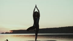 The tree pose in yoga. The girl is engaged in yoga at sunset Stock Footage