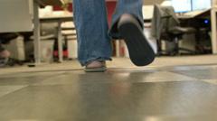 Camera behind men's feet walking through an office Stock Footage