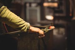 Glassblower working on a molten glass Stock Photos