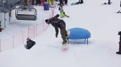 Snowboarder jump on kicker at ski resort in mountains. Extreme sport. People Stock Footage