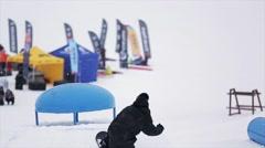 Snowboarder jump above kicker at ski resort in mountain. Dangerous hobby. People Stock Footage