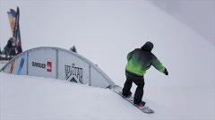 Snowboarder slide on iron curved trail at ski resort in mountains. Extreme sport Stock Footage