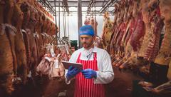 Butcher using digital tablet in meat storage room Stock Photos