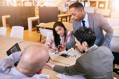 Businessman supervising his employees as they brainstorm and work together Stock Photos