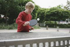 Disabled boy playing table tennis in park Stock Photos