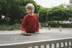 Portrait of happy disabled boy standing at table tennis table in park Stock Photos