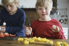 Portrait of disabled boy sitting by brother at table with vegetables in kitchen Stock Photos