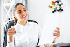 Happy smiling businesswoman analysing documents while having coffee break Stock Photos