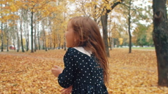 Back view happy cute little girl with curly hair runing through the autumn alley Stock Footage