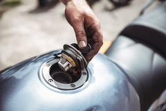 Mechanic opening a fuel tank of motor bike Stock Photos
