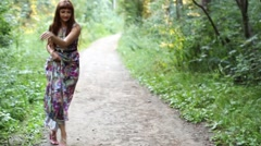 Happy girl dancing and smiling on a path in the woods Stock Footage