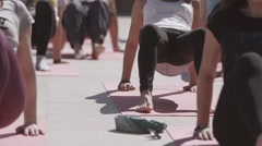 Young people do yoga at open playground in sunny morning, stretching. Health Stock Footage