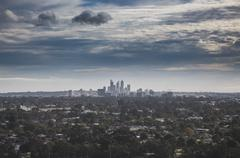 View of trees growing around city against cloudy sky, Perth, Western Australia, Stock Photos