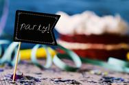 Confetti, streamers, cake and signboard with word party Stock Photos