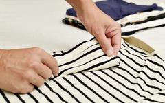 Young man folding clothes Stock Photos