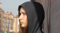 A hipster girl in a hoody with the hood on and loose multicolored hair against Stock Footage